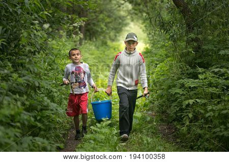 Gomel, Belarus - June 25, 2017: Village Children Go Fishing With A Bucket And Fishing Rods