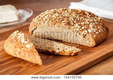 Delicious wheat-rye sourdough bread. Homemade whole grain bread sprinkled with oat flakes closeup