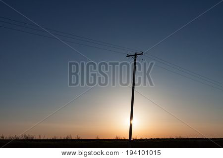 Silhouetted Power Pole On Canadian Prairie At Sunrise With Horizontal Crop