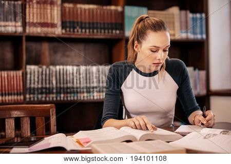 Female student taking notes from a book in library. Young caucasian student sitting at table doing assignments in college library.