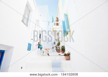 Young attractive woman wearing shorts and sandals, sitting on chair between white traditional greek houses and enjoying colours of authentic greek village full of flowers - Greece holidays concept