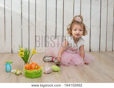 cute little girl sitting on the floor with flower pot in hands