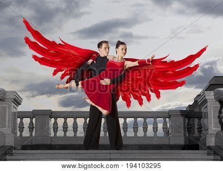 Angel wings. Pair of dancers dancing ballroom on sky background