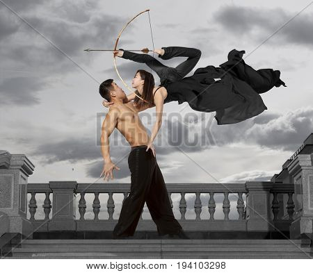 Archer. Pair of dancers dancing ballroom on sky background