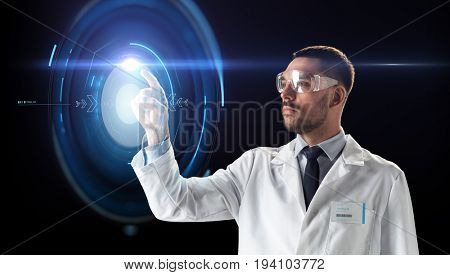 science, future technology and people concept - male doctor or scientist in white coat and safety glasses touching virtual projection over black background