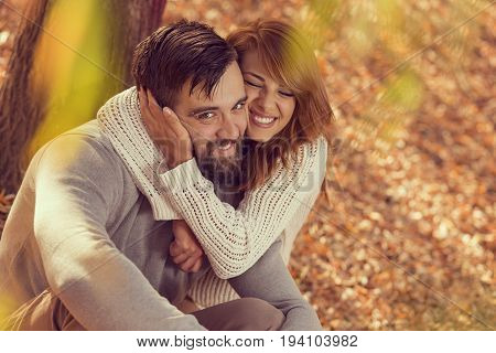 Couple in love sitting on autumn fallen leaves in a park under a tree hugging and enjoying a wonderful autumn day