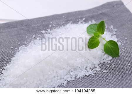 pile of coarse grained sea salt on grey place mat - close up