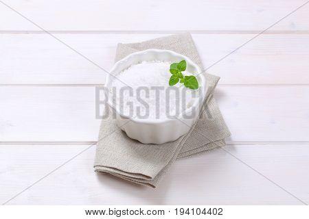 bowl of coarse grained sea salt on beige place mat