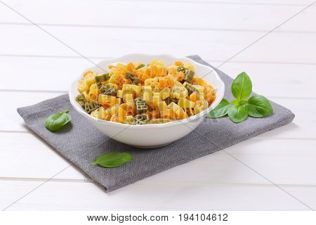 bowl of raw colored pasta on grey place mat