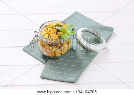 jar of raw colored pasta on grey place mat