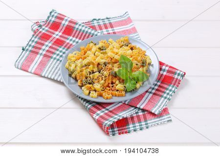 bowl of raw colored pasta on checkered place mat