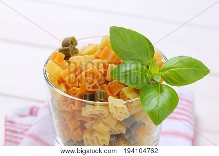 glass of raw colored pasta on checkered dishtowel - close up