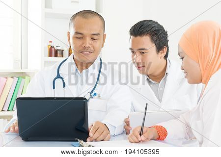 Hospital, medical education, health care, people and medicine concept - group of happy doctors with tablet pc and computers meeting at medical office. Southeast Asian Muslim.