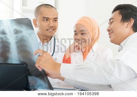 Surgeon and doctor analyzing x-ray together in medical office. Southeast Asian Muslim people.