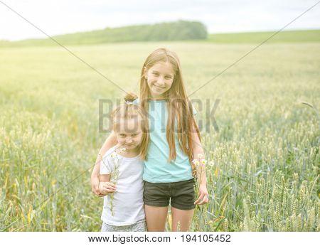 sibling sisters hugging each in the field