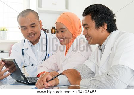 Group of doctors meeting at hospital office. Southeast Asian Muslim medical people.