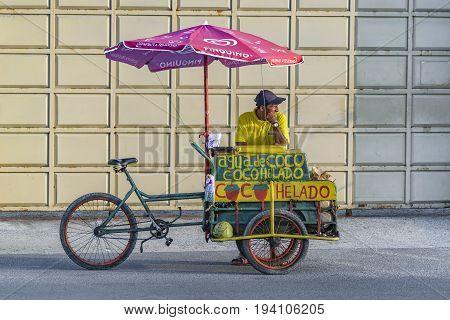 SALINAS, ECUADOR, JULY - 2016 - Street vendor selling traditional tropical coconut juice at sidwalk in Salinas Ecuador