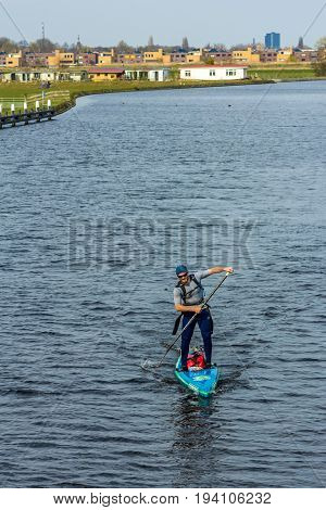 Zuid Holland the Netherlands - 9 April 2016: fit young man paddling stand up paddle board