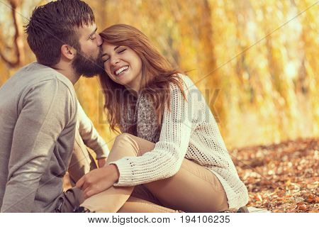 Couple in love sitting on autumn fallen leaves in a park enjoying a beautiful autumn day. Man kissing a woman in a forehead