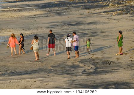 SALINAS, ECUADOR, JULY - 2016 - High angle long distant view of group of adult people walking at beach in Salinas Ecuador