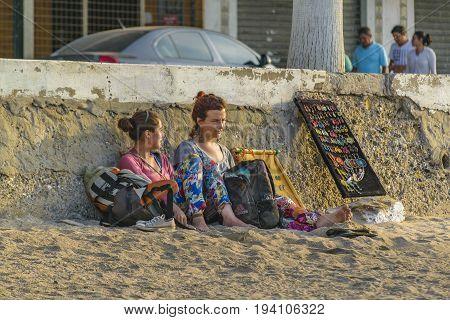 SALINAS, ECUADOR, JULY - 2016 - Two hippie style street vendor resting at Salinas beach Ecuador