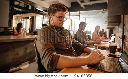 Young man sitting at cafe and using laptop computer with people in background.