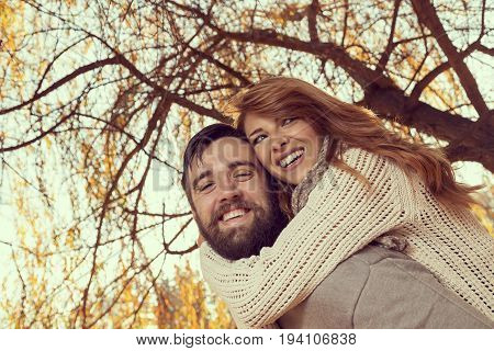 Couple in love having fun and fooling around on a wonderful autumn day in a park guy piggybacking his girlfriend