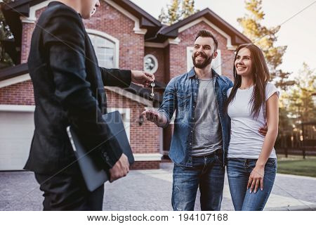 Happy couple is taking keys from their new house from broker and smiling.