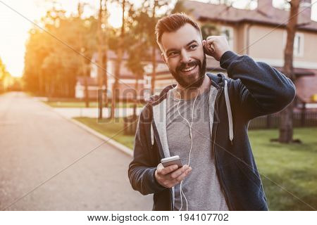 Handsome man in earphones is having rest and listening to music during running outdoors near modern private houses.