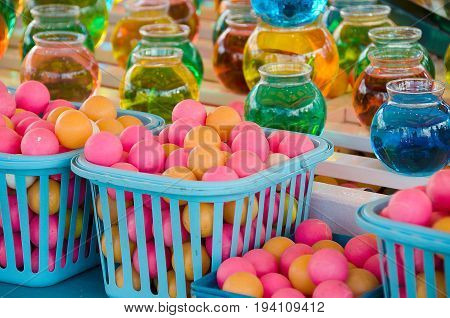 carnival game with colorful balls and water in glass bowls