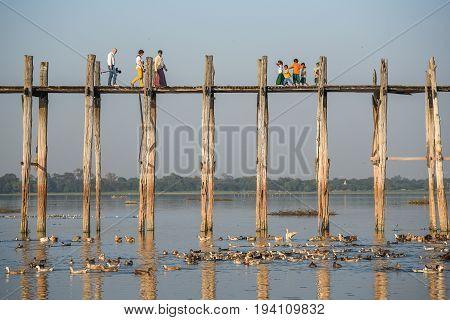 AMARAPURA MYANMAR - DECEMBER 23 2016 : Unidentified people walk on U Bein Bridge the oldest and longest teak bridge (Wooden footbridge) in the world near Mandalay.