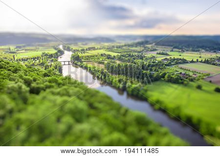 Aerial landscape view on Dordogne river with the old bridge and beautiful fields near Domme village in France. Tilt-shift image technic