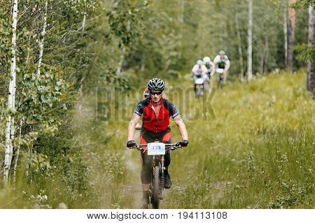 Revda Russia - July 1 2017: group athletes cyclists riding trail in green forest during Regional competitions on mountain bike