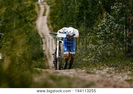 Revda Russia - July 1 2017: man cyclist with mountainbike long uphill climbs during Regional competitions on mountain bike