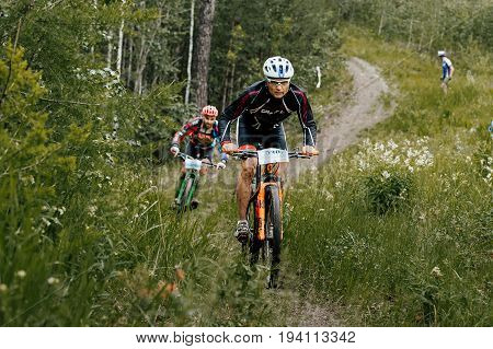Revda Russia - July 1 2017: rivalry between two cyclists athletes on a forest trail during Regional competitions on mountain bike