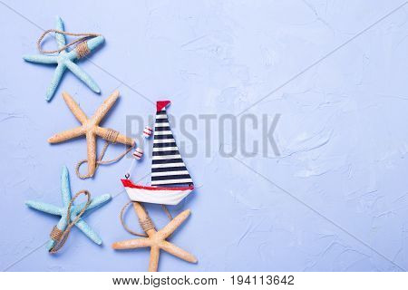 Star fishes and decorative wooden toy boat on textured blue background. Top view. Place for text.