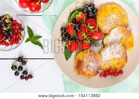 Golden cottage cheese pancakes with fresh berries on a plate on white wooden background. Top view. Proper nutrition.