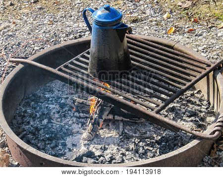 Blue tea water kettle on grill in fire pit at campground