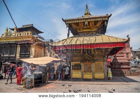 KATHMANDU NEPAL - APRIL 7 2016 : People walk around Stupa in Swayambhunath (monkey temple) one of famous landmarks in Kathmandu valley Nepal