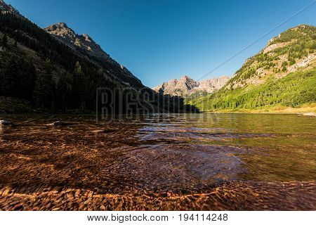Maroon Bells with shallow transparent water in Lake in Fall