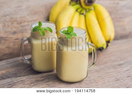 Banana Smoothies And Bananas On An Old Wooden Background