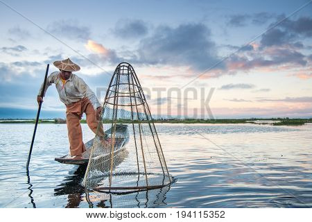 NYAUNGSHWE MYANMAR - DECEMBER 18 2016 : Burmese Intha fisherman with traditional fishing net on the boat in Inle lake at sunrise.