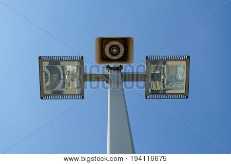 A vintage loudspeaker and modern light pole against the blue sky