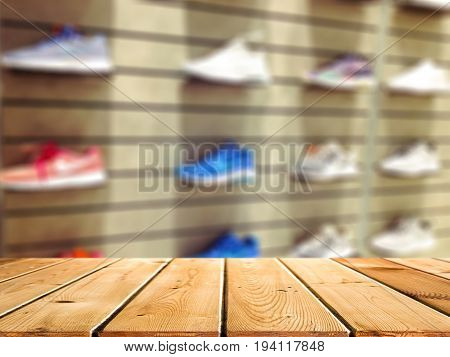 Abstract blur and defocused shoe department in shopping mall and retail store interior for background and empty wooden table space platform for present product.