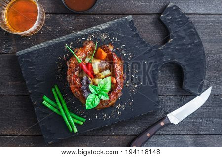 Crown roast of pork with grilled vegetables and whiskey sauce, top close view