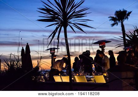 San Diego USA - March 8 2014: People outside in famous Hotel del Coronado bar and restaurant at night in California with sunset and illuminated objects