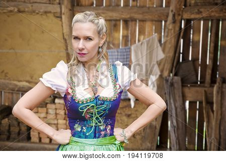 portrait of angry blonde woman in dirndl in front of clothesline