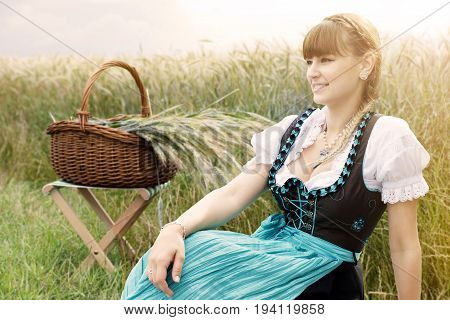 young woman in dirndle sitting at field next to basket with wheat