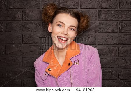 Redhead girl with hair buns wearing pink jacket with orange color smiling standing against brown brickwall.