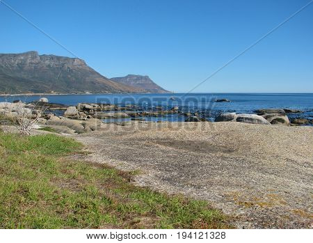 CLIFTON,  CAPE TOWN, SOUTH AFRICA, HUGE BOULDERS AND GRASS IN THE FORE GROUND, AND A MOUNTAIN IN THE BACK GROUND 24onr
